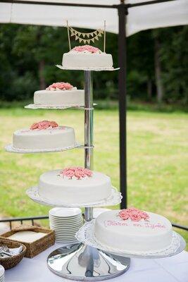 Bruidstaart met roze rozen in het midden